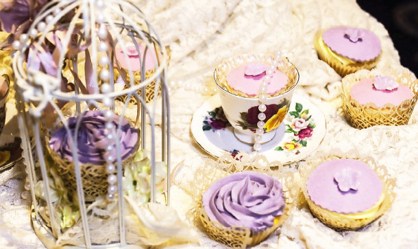The new Mrs Devine decorated her wedding cake's table with a lace cloth, pearls, vintage tea cups and saucers and vintage cupcakes in colours that would match her bridesmaid's gown.