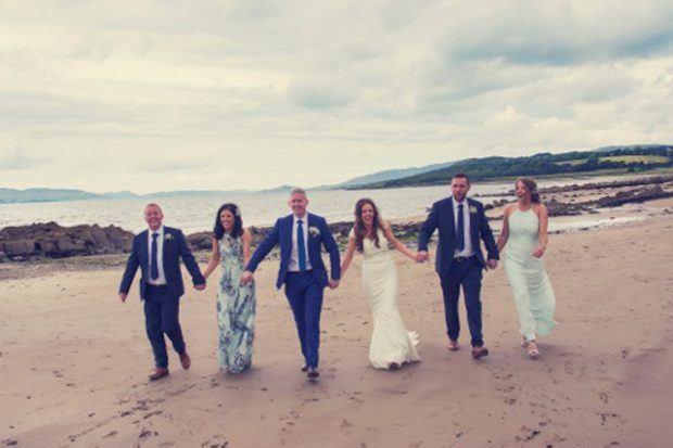 Newlyweds Kelly and Paul Connolly enjoy a summer stroll on the beach alongside their maid of honour, Emma McGonagle, best man, Peter Foley, bridesmaid, Emma Griffiths and groomsman, Darren McCrossan.