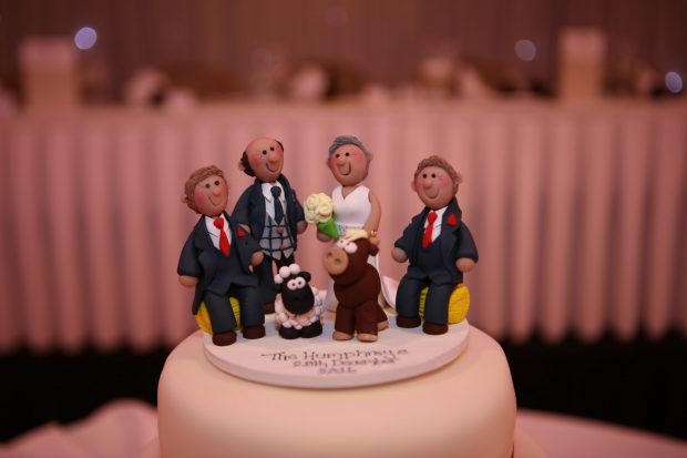 Alison and Kenny's ivory three-tier wedding cake topper featured a cute clay model of themselves and the groom's two sons, Stephen and Andrew Humphreys.