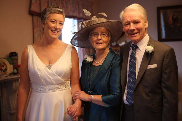 Beautiful bride Alison Humphreys (née Stewart) smiles alongside her beloved parents, Rene and Patterson Stewart on the day of her wedding.